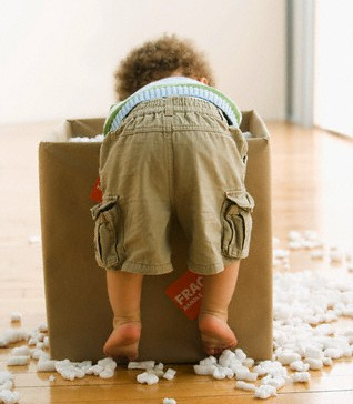 Toddler with cardboard box and packing peanuts